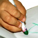 Child writing with crayon.